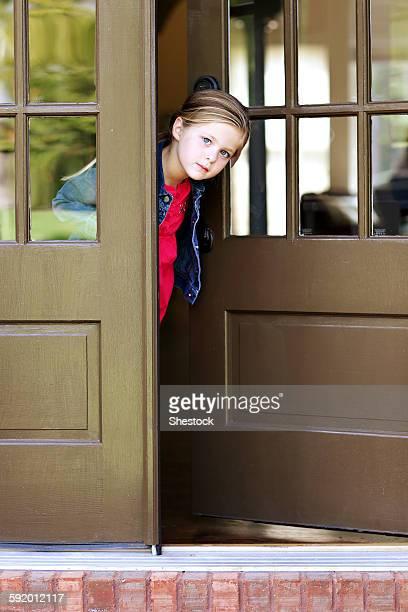 Curious girl standing in doorway