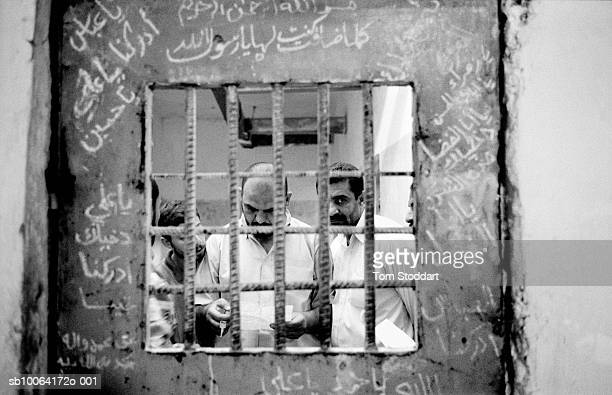 , Curious Iraqis read through files at the notorious Ashair Prison in Basrah. Many of their friends and relatives had been imprisoned and tortured by...