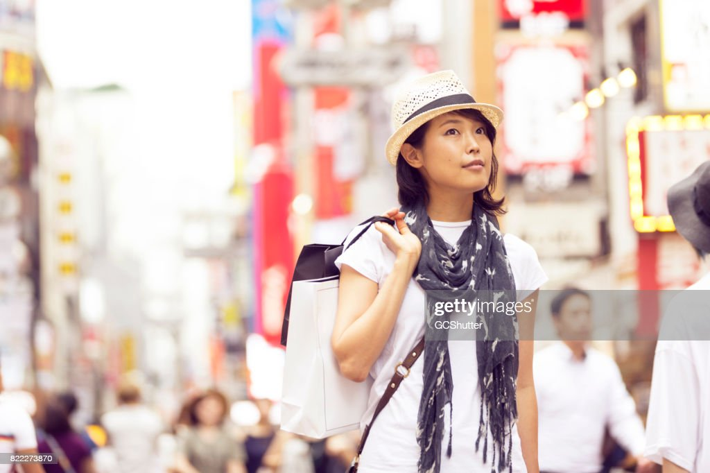 Curious Japanese woman shopping in the streets of Shibuya : Stock Photo