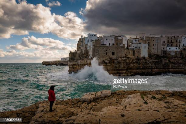 Curious lady admires the storm and the waves that hit the Lama Monachile cliff in Polignano a Mare on January 16, 2021. The arrival of the...