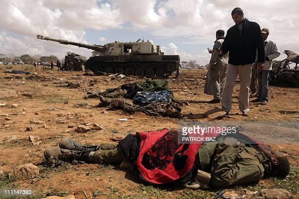 Curious Libyan onlookers take pictures of dead African teenagers members of Moamer Kadhafi forces on March 20 2011 in alWayfiyah 35 km West of...