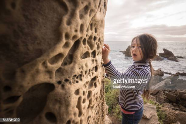 Curious little girl inspecting rock formations on beach cliffs