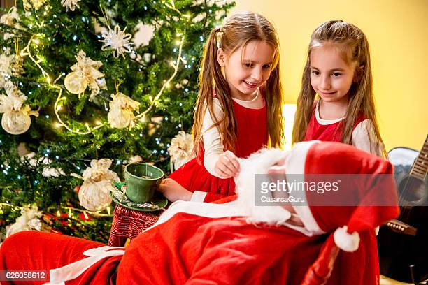 curious little girls teasing santa - naughty santa stock photos and pictures