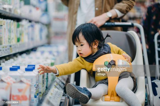 Curious little toddler girl grabbing a bottle of fresh milk from the fridge while sitting on shopping cart grocery shopping with mother