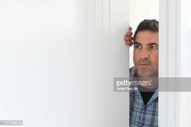 curious man looking through a door - rafael ben ari fotografías e imágenes de stock