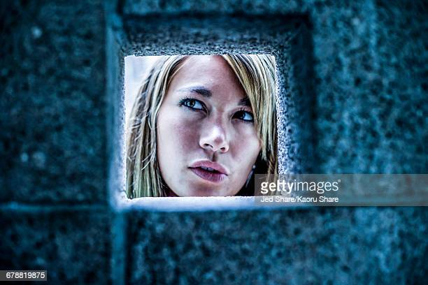 Curious Mixed Race woman looking through stone wall