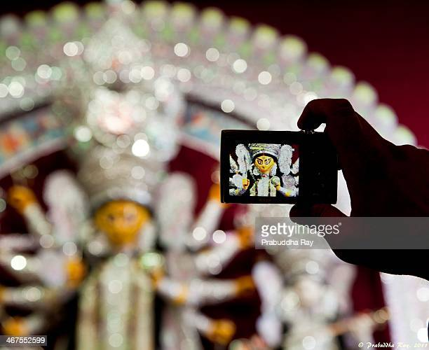 CONTENT] A curious onlooker capturing the goddess Durga during the auspicious occasion of Durga Puja at Kolkata