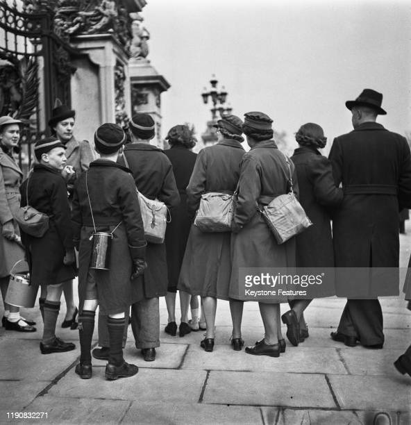 Curious onlookers outside the gate of Buckingham Palace in London on Investiture Day during World War II April 1941