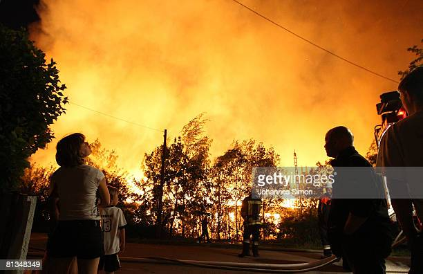 Curious onlookers watch the fire brigade fighting a major fire on June 2 2008 in Plattling Germany The fire destroyed paper and combustibles...