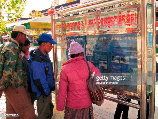 Curious pedestrians view pictures and read accounts of horror road accidents in display Shigatse Tibet