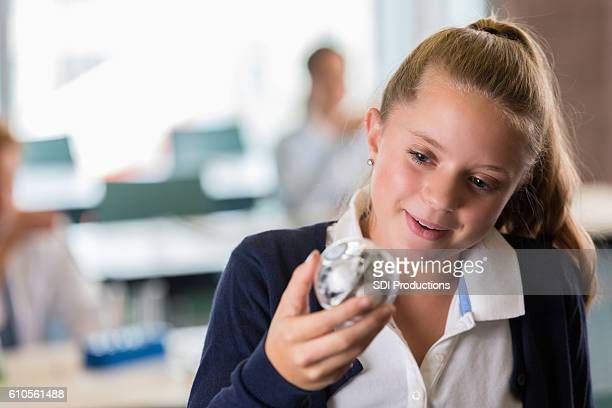 Curious preteen girl looking at robot in STEM class