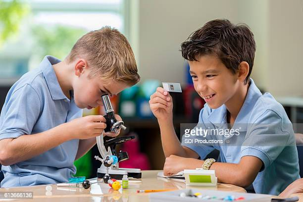 Curious private STEM schoolboys work with microscope