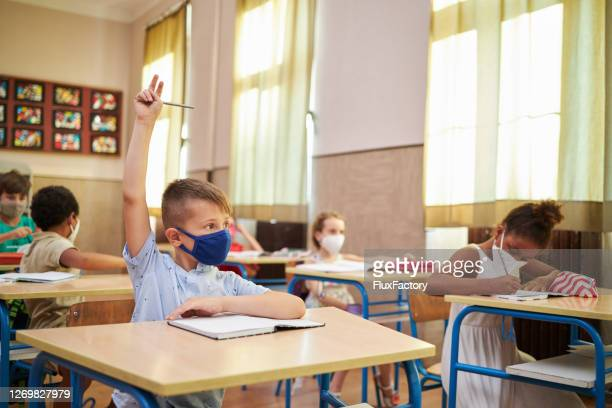curious school boy raise his hand to ask a teacher about subject he don't understand - primary school child stock pictures, royalty-free photos & images