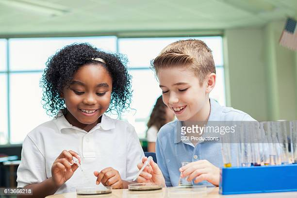 Curious STEM school friends work on science experiment