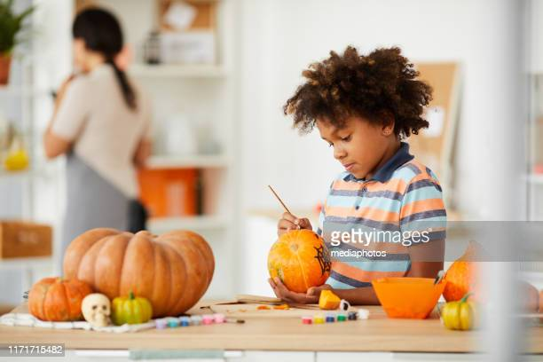 curious talented boy with afro hairstyle standing at counter with art and craft tools and painting pumpkin with paintbrush - october stock pictures, royalty-free photos & images