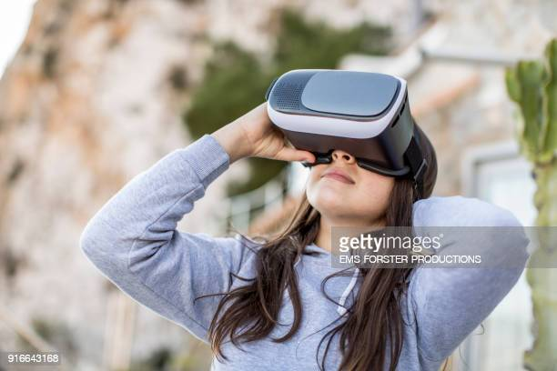 curious teenager girl using virtual reality headset outdoors
