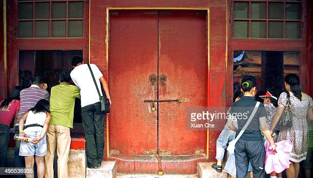 CONTENT] Curious tourists peeking through windows in the Forbidden City in Beijing China Royal Palace of Chinese Dynasties