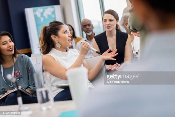 curious woman asks question during business conference - town hall stock pictures, royalty-free photos & images