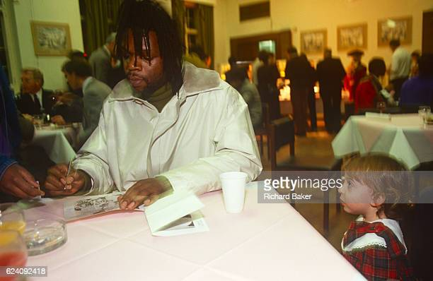 Curious young girl looks at the musician, Jazzy B during a Mayor's Christmas lights event in Brixton town hall in December 1989, London England.