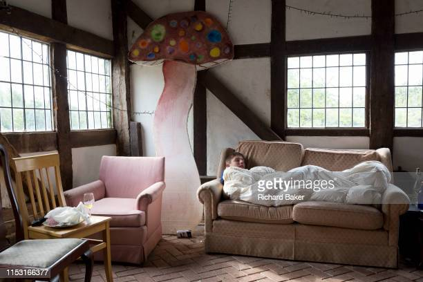 Curled up under a duvet on a sofa a teenager sleeps off a late night the morning after a birthday party in a countryside barn on 23rd June 2019 in...