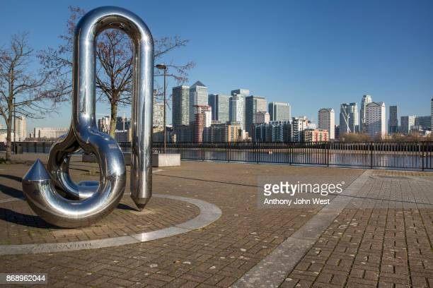 Curlicue, a sculpture by William Pye, Greenland Dock, with the International banks on Canary Wharf across the river, London