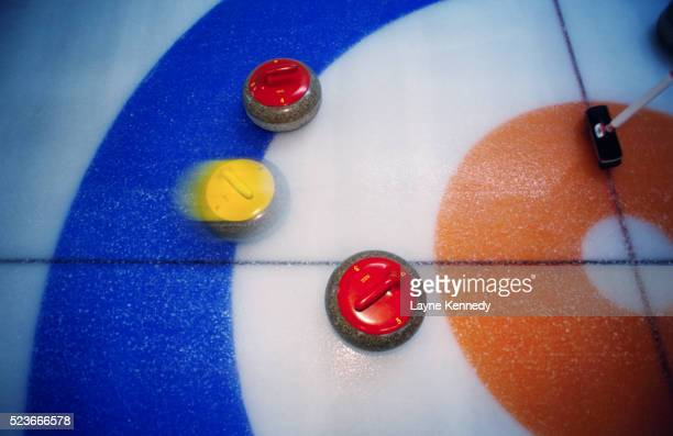 Curling Stones Moving Over the Ice