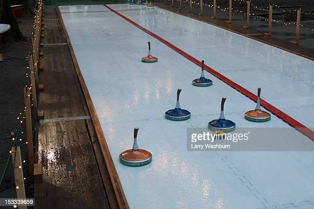 curling stones on a curling sheet - カーリング ストックフォトと画像