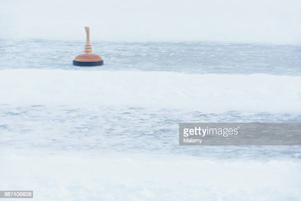curling stones on outdoors curling rink. ice stock sport. - winter sports event stock pictures, royalty-free photos & images