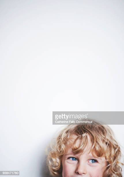 Curly blond boy against white backdrop