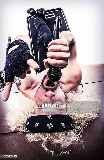 Curly blonden langhaarigem Rocker auf den Kopf am Boden liegen, Gesang
