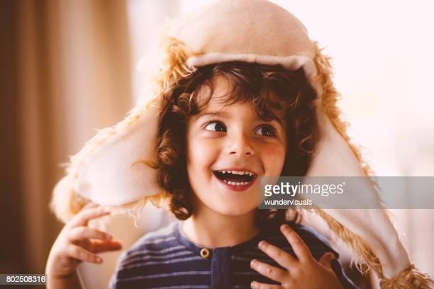 Lockige Jungen spielen zu Hause Hut einen lustigen Pelz