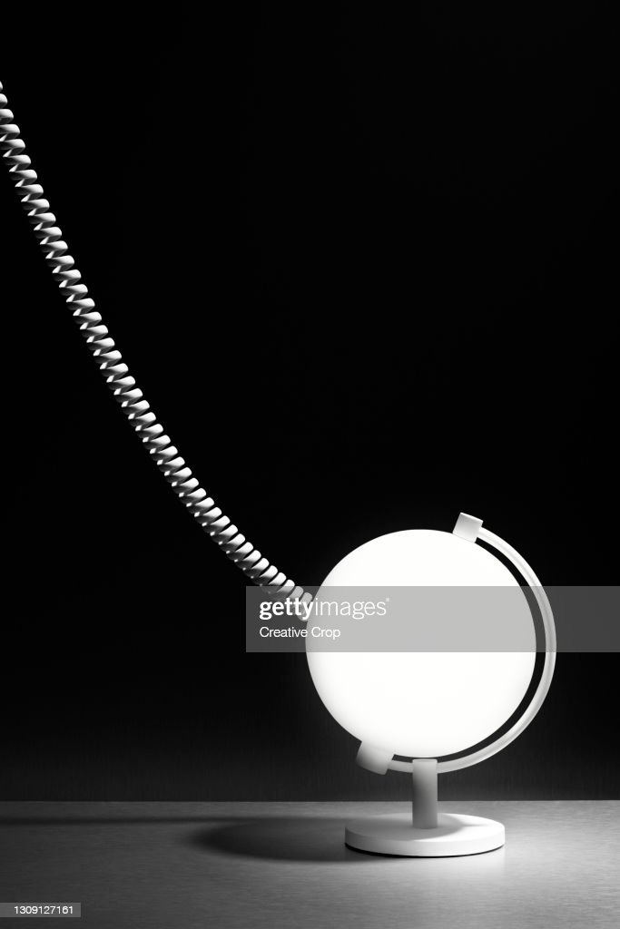 A curly cable attached to a white globe against a black background : Stock Photo
