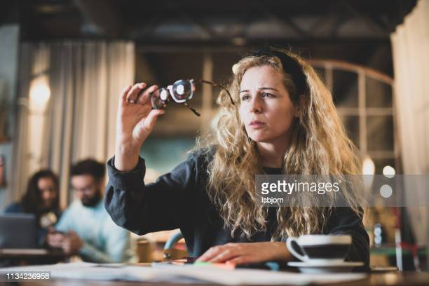 curly female student holding eyeglasses in bookstore.. - extra long stock pictures, royalty-free photos & images