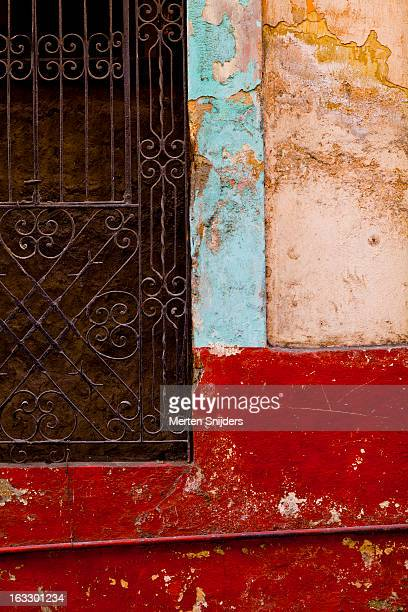 curly fence and colorful eroded wall - merten snijders stockfoto's en -beelden