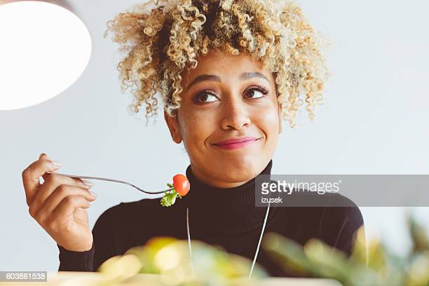 Curly hair young woman eating salad