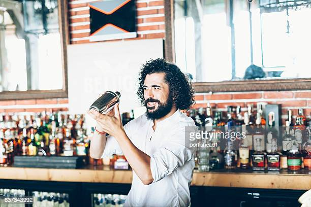 Curly haired bartender making cocktails
