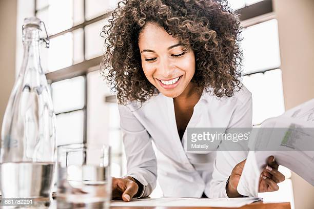 Curly haired business woman looking down at paperwork smiling
