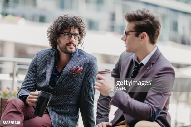 Lockigen Haaren Geschäftsmann sitzt auf der Bank mit einem Kollegen in der Kaffeepause