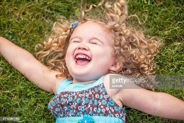 Curly langhaarigem kleines Mädchen Leg dich auf Gras Lachen