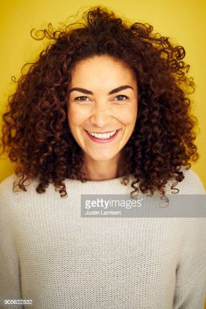 Curly haired mixed race woman laughing or smiling openly at camera on bright yellow backdrop