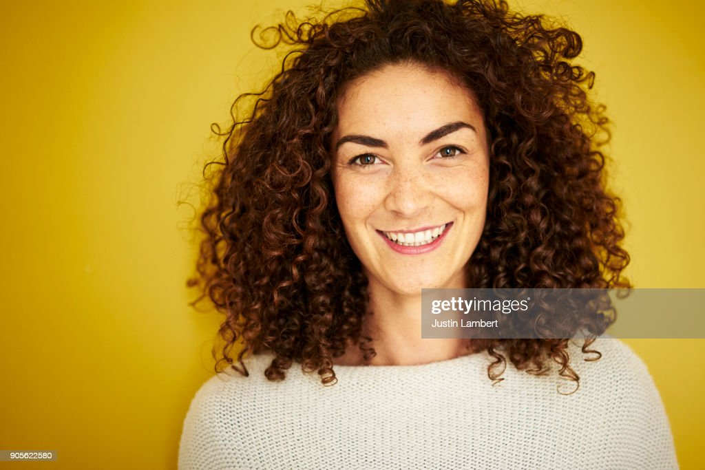 Curly haired mixed race woman smiling openly at camera on vibrant yellow backdrop : Foto de stock