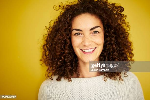 curly haired mixed race woman smiling openly at camera on vibrant yellow backdrop - toothy smile stock pictures, royalty-free photos & images