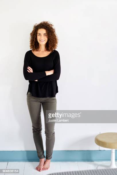 curly haired mixed race woman stands in her bedroom against a plain wall - pieds nus photos et images de collection