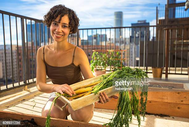 Curly Haired Woman Smiling on Rooftop Garden