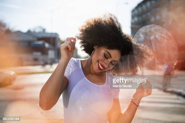curly haired young woman dancing on street - joy stock pictures, royalty-free photos & images