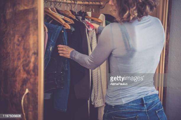 curly woman getting dressed in the morning - dress over pants stock pictures, royalty-free photos & images