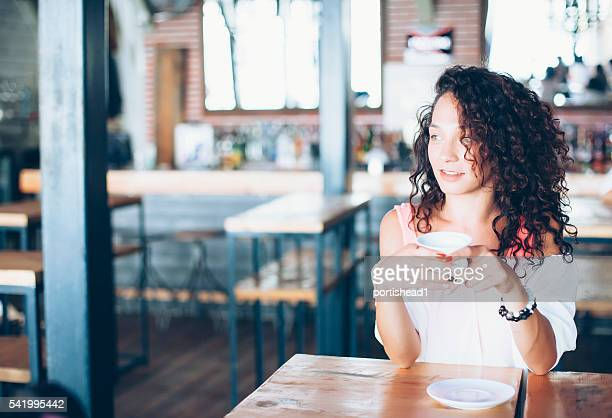 Curly young woman drinking coffee in a bar