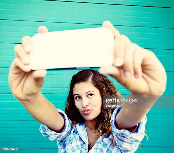 curly-haired beauty takes trout-pout selfie - puckering stock photos and pictures