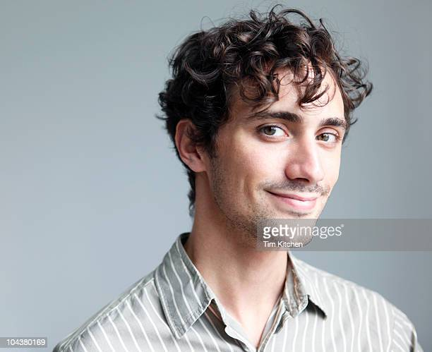 Curly-haired dimply-cheeked man smiling, portrait
