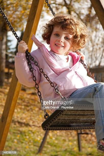 Curly-haired girl on swing